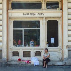 La vita parallela lungo Knez Mihajlova, dove di fianco ai negozi tradizionali alcune signore vendono oggetti fatti a mano