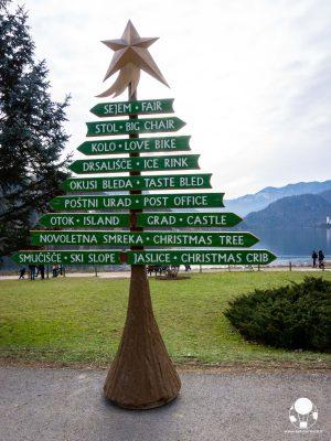Mercatino di Natale sul Lago di Bled, albero natalizio in legno con indicazioni