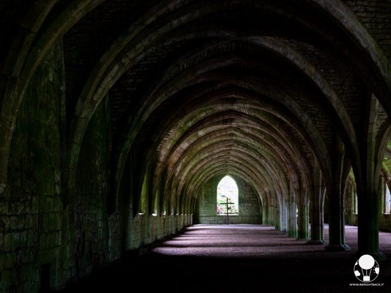 Gli archi a volta della piccola navata del chiostro, in fondo alla quale c'è anche una piccola croce