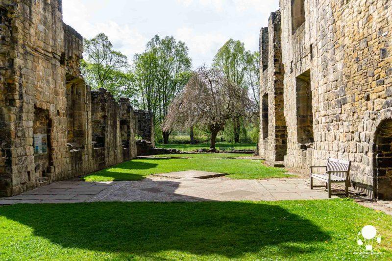 Giardino con panchina e salici in uno dei cortili dell'abbazia di Kirkstall, Leeds