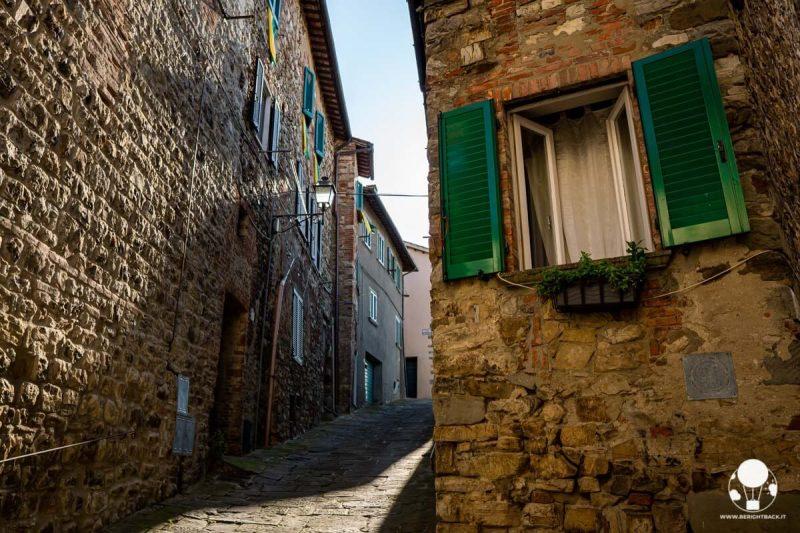 Vicolo in salita e persiana aperta in primo piano, Lucignano